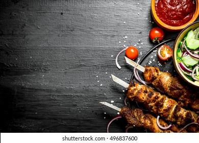 Shish kebab of pork and salad. On the black wooden table.