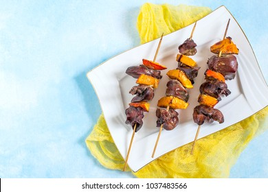 Shish kebabs from chicken liver with tangerines on wooden skewers. Prepared on grill