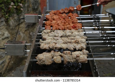 Shish kebabs rotate on the grill with electric motors