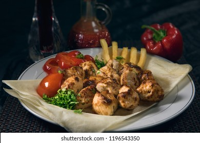 Shish Tawook in a platter ready for lunch or dinner at restaurant with fresh vegetables, capsicum and tomato sauce (Arabic Turkish food)
