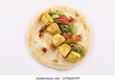 shish tikka sandwich curry tandoori chicken with salad in open naan bread isolated top view on white background