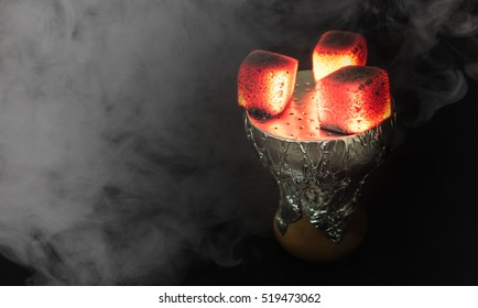 Shisha bowl with craft tobacco and red coil with hookah smoke background.