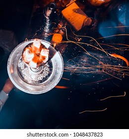 Shisha hookah with red hot coals. Sparks from breathe. Toned image. Modern hookah with coconut charcoal for relax and shisha smoke. Hookah and sparks from coals. square cropping close up view