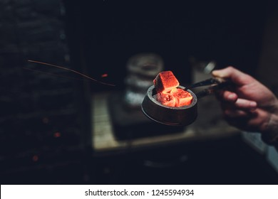 Shisha hookah with red hot coals. Sparks from breathe. Modern hookah with coconut charcoal for relax and shisha smoke. Hookah and sparks from coals. Another view. Shisha, spark,spark, hookah sparks.