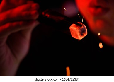 Shisha hookah, red hot coals. Man blows coals for, sparks fly.