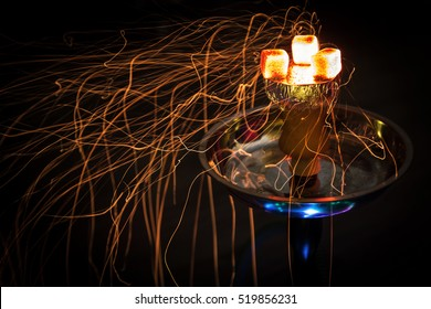 Shisha hookah with red hot coals. Sparks from breathe. Modern hookah with coconut charcoal for relax and shisha smoke.