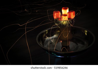 Shisha hookah with red hot coals. Sparks from breathe. Modern hookah with coconut charcoal.