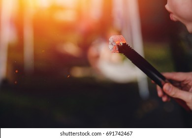 shisha hookah red hot coals, man blows coals for , sparks fly. Concept vacation with friends in nature