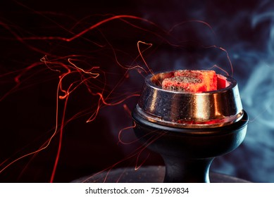 Shisha hookah with red hot coals. Sparks from breathe. Modern hookah with coconut charcoal and shisha smoke. Hookah and sparks from coals.