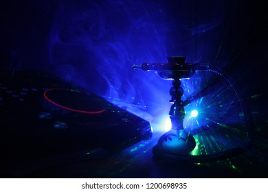 Shisha party club concept. Dj mixer with on dark nightclub background with stylish oriental shisha. Selective focus