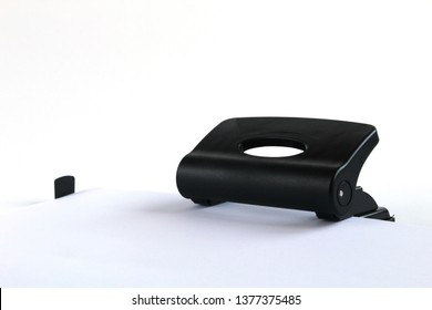 Shit of paper in hole puncher.. Black office puncher isolated on white background