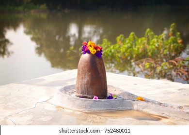 Shiva lingam decorated with flowers on the bank of holy river. Holy symbol of Hindu God Lord Shiva, India
