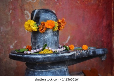 Shiva lingam of Lord Shiva (Indian God) with flowers offered on it beautifully in a temple of Varanasi. Closeup shot of Shiva linga,decorated with bilva (bael) leaves, parijat and zendu flowers