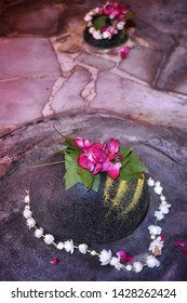 Shiva Lingam of Lord Shiva (Indian God) decorated with bilva (bael) leaves, parijat and zendu flowers in a temple of Varanasi. Closeup shot of old decorated Shiva Lingam