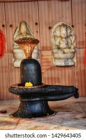 Shiva Lingam of Lord Shiva (Indian God) decorated beautifully with bilva (bael) leaves, parijat and zendu flowers in a temple of Varanasi. Closeup shot of old decorated Shiva Lingam