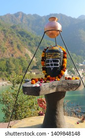 Shiva Lingam in Rishikesh against the backdrop of mountains and Ganges River. The symbol of Shiva is decorated with a flower garland and tilak. Religious object of worship of traditional India.