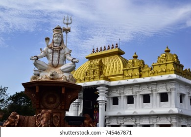 Shiva statue near hinduism temple with bright golden roof. Sri Ramayana Darshanam & BharatMata Sadanam, Kanyakumari, India