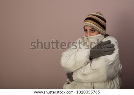 3cc6dd6145a28b Shivering cold woman in warm winter clothing wearing a thick jacket and  knitted cap as she