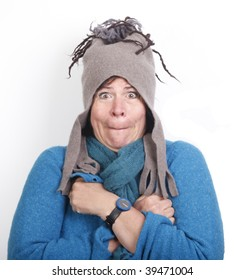 Shivering middle aged woman in funny felt cap and in blue sweater