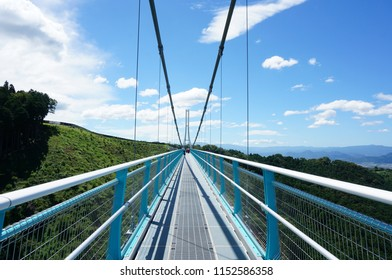 Shizuoka /Japan- August 8, 2016 : The view under blue sky of the Hakone Seiroku Mishima skywalk is the longest pedestrian suspension bridge in Japan above the green mountain and forest in summer