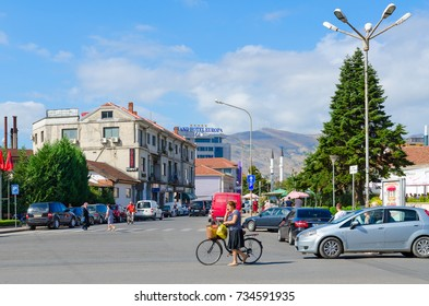 SHKODER, ALBANIA - SEPTEMBER 6, 2017: Street (Rruga Vilson), Grand Hotel Europa in city center of Shkoder, Albania. Unknown people ride bicycles and walk down street