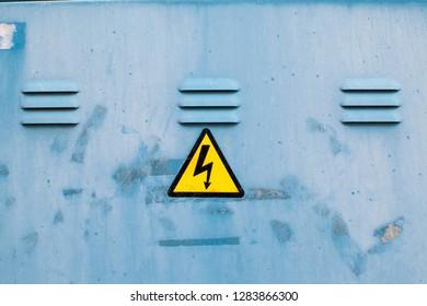 Shock hazard warning sign on an old metal door
