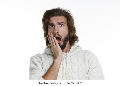Shock, surprise and astonishment concept. Picture of surprised young male with fuzzy beard and voluminous hair opening mouth widely and holding hand on his cheek, shocked with intriguing gossip