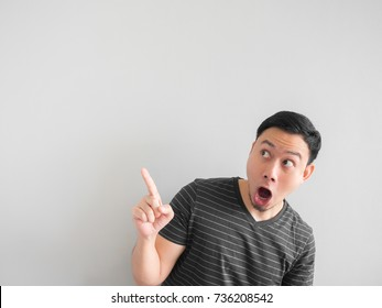 Shock and surprise face of Asian man point on empty space.
