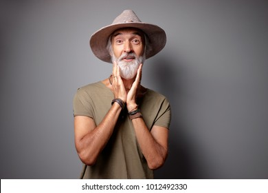 Shock and surprise! Studio portrait of amazed senior man with gray beard and hat.