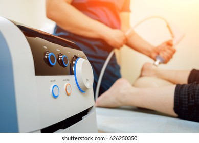 Shock wave therapy. The magnetic field, rehabilitation. Physiotherapist doctor performs surgery on a patient's heel