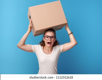 shocked active woman in white shirt with a cardboard box on head on blue background