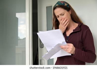 Shocked adult woman  (female age 25-35) reading a letter outside a home front door.  Real people. Copy space