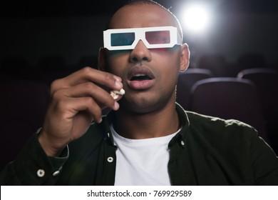 shocked african american man in 3d glasses watching movie in cinema