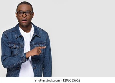 Shocked african man student pointing finger aside at copy space surprised astonished looking at camera isolated on white grey studio background, stunned black guy advertise unbelievable presentation