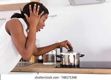 Shocked African Woman Looking At Spilling Out Boiled Milk From Utensil In Kitchen