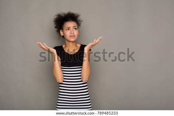 Shocked african-american woman with arms up in air in full disbelief. Surprised girl portrait, gray background. Omg, wtf, human emotions concept