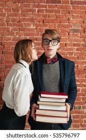 Shocked after woman kiss student, free space. Young couple, girl kissed nerd, man with books dazedly looking at camera. Love, relationship, beauty and downer concept