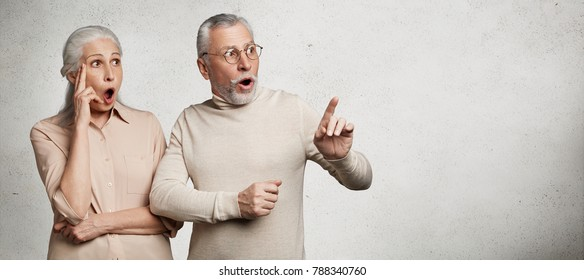 Shocked amazed senior grey haired old female and male dressed casually, indicate with great surprisment aside,notice something shocking, isolated over white concrete background with copy area
