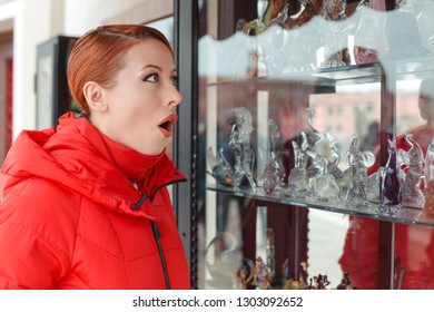 Shocked, amazed stunned young woman looking at a souvenir shop vitrine window in Italy Murano Island. Irish model in red winter coat clothing redhead hair. Amazing murano glass figurines on background