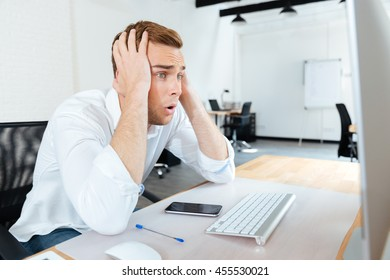 Shocked amazed young businessman using computer at workplace