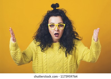 Shocked amazed young woman, standing yellow background. Human emotions, facial expression concept. Girl with curly hair in glasses, yellow knitted sweater. Horrible, stress, shocked