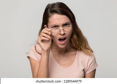 Shocked angry young woman in disbelief lowering glasses looking at camera with indignation isolated on grey blank studio background, confused girl frowning touching eyeglasses feeling flabbergasted