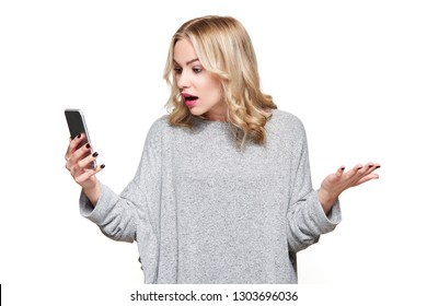 Shocked angry young woman looking at her mobile phone in disbelief. Woman staring at shocking text message on her phone, isolated over white background.