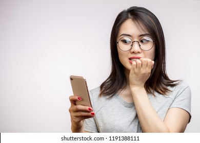 Shocked anxious surprised asian woman reading on smart phone terrible news, one hand cover mouth in fear, isolated on white background.