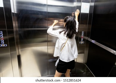 Shocked asian child girl is stuck in an elevator,sad teenager girl standing alone and screaming in a despair suffer from claustrophobia in elevator,worried woman is experiencing fear,stress,anxious