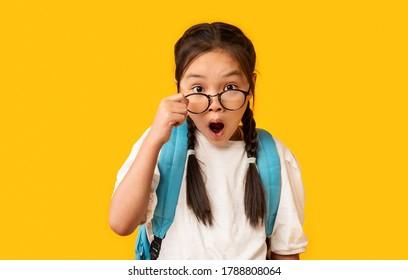 Shocked Asian Elementary School Girl Looking At Camera Above Glasses Posing Over Yellow Background. Studio Shot