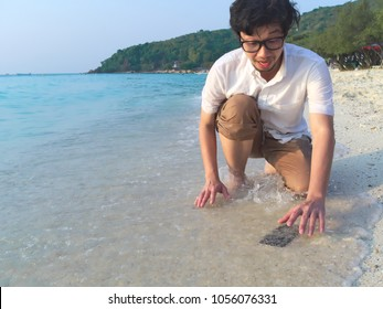 Shocked Asian man dropping mobile smart phone on tropical sandy beach of sea. Accident and insurance electronic equipment concept
