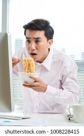 Shocked Asian white collar worker looking at computer screen while eating instant noodles with chopsticks, waist-up portrait shot