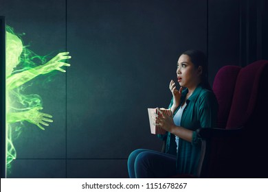 Shocked asian woman watching scary movie with popcorn at home