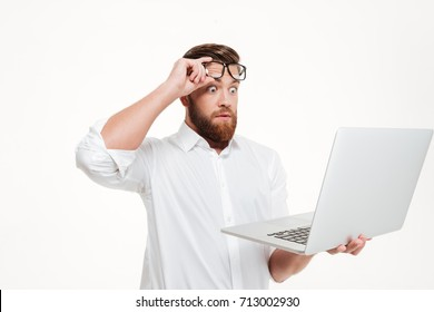 Shocked astonished man in eyeglasses looking at laptop screen isolated over white background